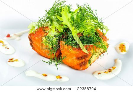 fried salmon fish with fresh lettuce leaves and fennel closeup