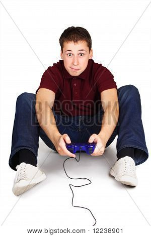 Young Man Sitting On Floor, Holding Joystick And Playing Console Games, Exciting Face, Isolated