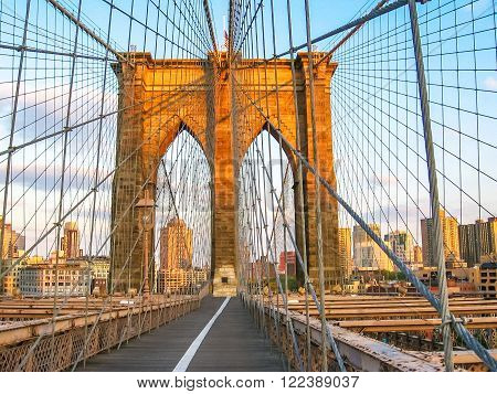 Spectacular views of the Brooklyn Bridge with all its characteristic metal wires and the pedestrian walkway at sunset, New York, United States.
