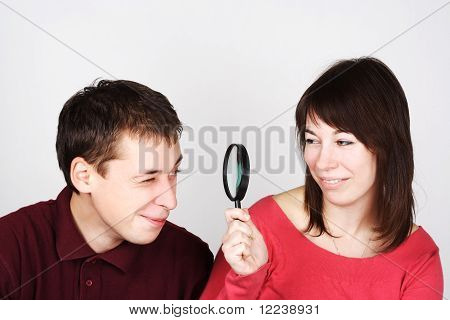 Young Man And Woman Looking Through Magnifier On Each Other