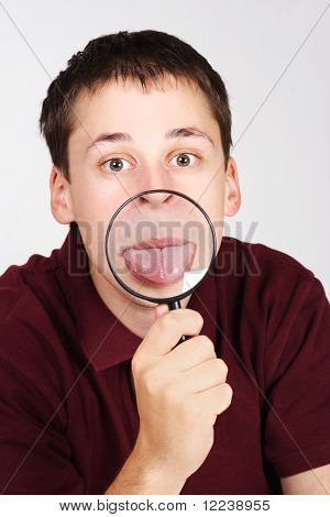 Joven con lupa y mostrando la lengua a través de él