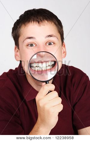Young Man Holding Magnifier And Showing Teeth Through It