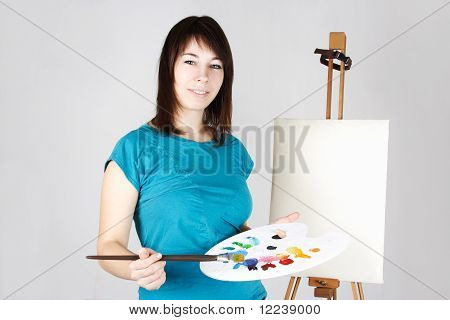 Young Girl In Blue Shirt Standing Near Easel, Holding Brush And Palette, Smiling