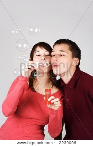 Young Brunette Man And Woman In Red Shirts Blowing Out Soap Bubbles