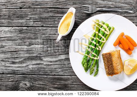 grilled hake served with asparagus piece of lemon baby carrots and the hollandaise sauce on the white platter on the old rustic table view from above
