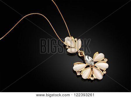 Golden Jewellery pendant with diamonds on darck background