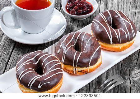 Donuts with Chocolate Icing a cup of tea top view