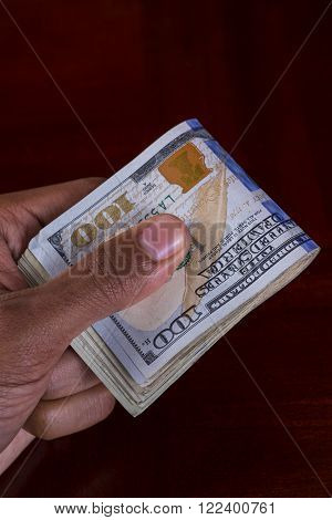 Hand full of money holding 100 dollar bill