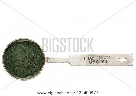 Nutrient-rich organic chlorella powder - isolated measuring metal tablespoon, top view