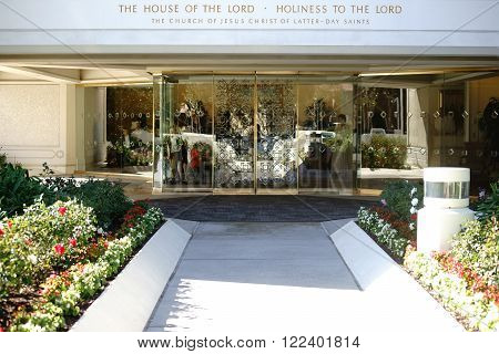 SAN DIEGO, UNITED STATES - DECEMBER 25: The gold ornamented glass entrance of the San Diego California Temple with flower beds in front of the building on December 25, 2015 in San Diego.