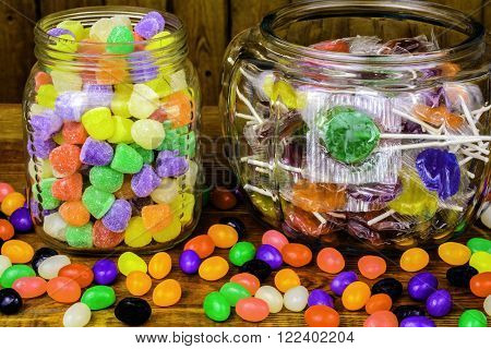 assorted glass jars of lollipops gumdrops jelly beans on wood background