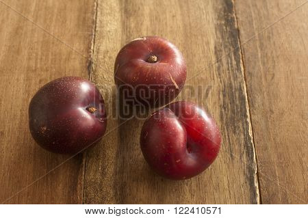 Three ripe red home grown plums on a wooden surface
