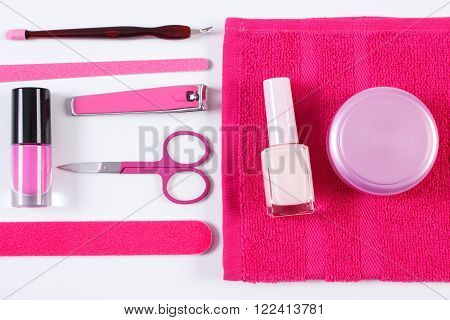 Cosmetics and set of manicure or pedicure tools nail file nail polish and remover scissors nail clippers fluffy towel concept of nail care