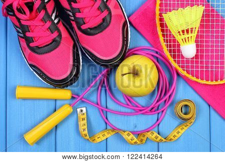 Pair of pink sport shoes fresh apple and accessories for sport on blue boards healthy and active lifestyles