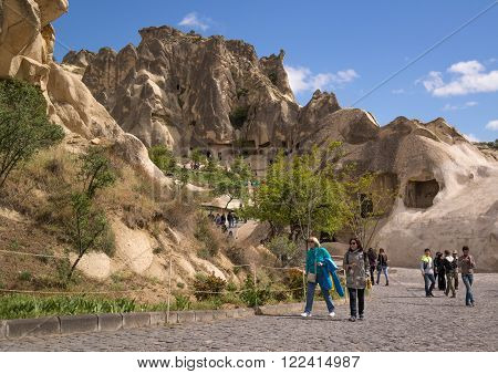Cappadocia Turkey - April 29 2014: Tourists visiting Cave Church at Goreme in Nevsehir. There are more than 10 cave churches in Goreme Open Air Museum. They form the largest monastery complex carved into the rock formations.