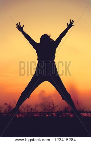 Silhouette Of Woman Jumping Against Sunset. Young Girl Enjoying The View.