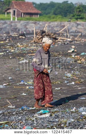 UBUD BALI INDONESIA - MARCH 19 2015 : Unidentified old poor woman collects plastic bottles to the trash