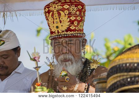 UBUD, BALI, INDONESIA - MARCH 19, 2015 : Unidentified Indonesian people celebrate Balinese New Year and the arrival of spring. Old Brahmin conducts religious ritual on the beach Ketewel