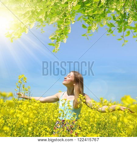 Young happy woman on blooming rapeseed field in spring
