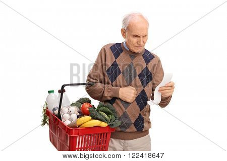 Senior man carrying a shopping basket full of groceries and reading a shopping list isolated on white background
