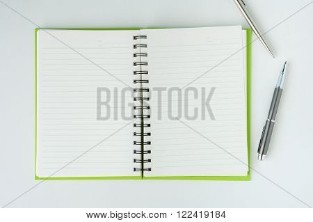 Open notebook with metallic ball pen. Top view.