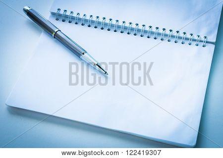 Open notebook with metallic ball pen. Selective focus an blue tone.