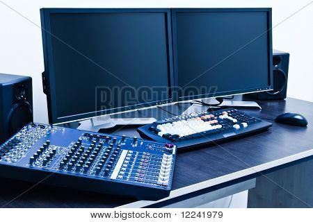 professional editing station with audio mixer and dual monitor setup