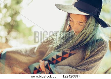 Attractive fashionable girl in a hat and poncho walking outdoor