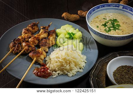 Asian satay meat skewers with rice cucumber salad and peanut sauce in plates and bowls on a dark wooden table selected focus