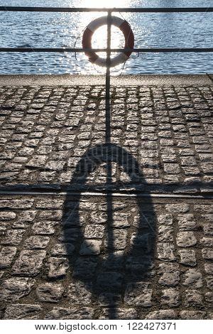 lifebuoy in the back light on the railing and a long shadow on the pier with cobblestones in cargo port concept for safe transactions
