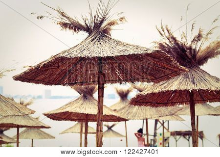 Beach sunshade parasols made of dried straw. Straw beach umbrellas. Toned image. Shallow depth of field. Selective focus.