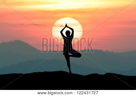 Silhouette young woman practicing yoga on the mountain at sunset twilight sky.
