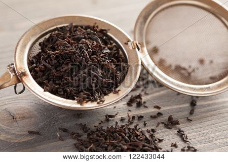 Black tea in metal strainer on a wooden table closeup shot selective focus