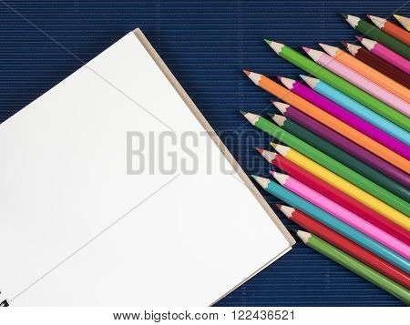Stack of color pencil and blank notebook on blue corrugate paper background (Business object)