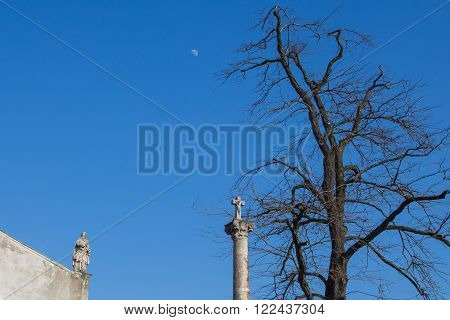 Part of a roof of Church of Saint Cross with a statue. Column with a cross under old big tree. Bright blue sky with a moon. Devin Bratislava Slovakia.