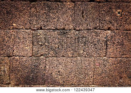 Uneven weathered pitted background texture of an old stone wall on a building