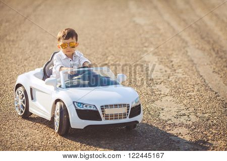 The young driver,a boy with brunette short hair,mirrored sun glasses yellow,in white shirt posing on a mountain road 