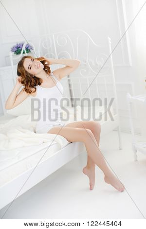 Young beautiful redhead woman with long curly hair ,dressed in a white nightgown wakes up in the morning on a soft pillow in a white bed in bright bedroom in a beautiful vintage white bed