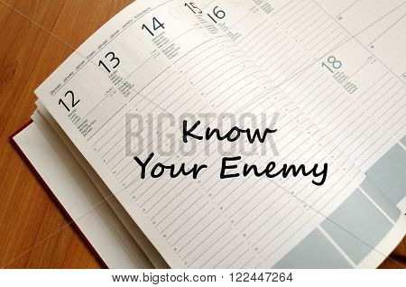 Know your enemy text concept write on notebook