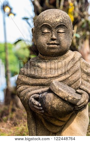 Old statue of a little monk standing and holding monk's alms-bowl