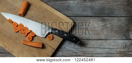 freshly cutted carrots on old wooden table background with knife