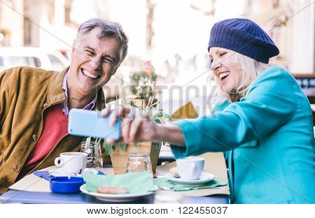 Senior couple taking a selfie in the city center cafe ** Note: Shallow depth of field