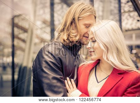 Couple passionated moment in an urban area. Man whispering in his girlfriend ear. ** Note: Shallow depth of field