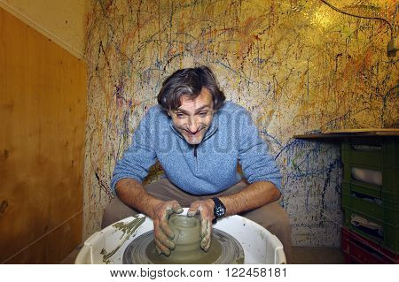 a happy man shaping clay pottery bowl