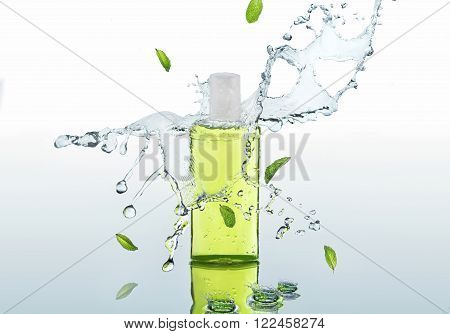 The herbal green moisturizing shampoo stands on the water background with splashes and mint leaves