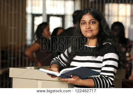 Young Indian college student holding book inside campus