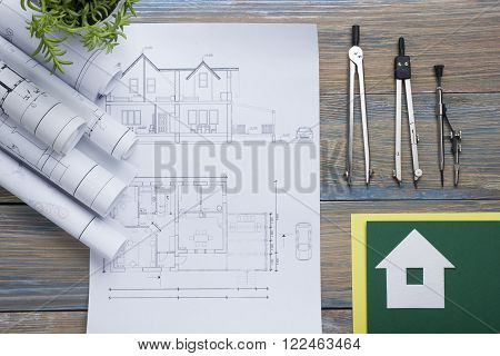 Real Estate concept. Architectural project, blueprints, blueprint rolls and  divider compass on vintage wooden table. Top view. Construction background. Engineering tools. Architect workplace