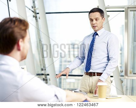 two caucasian corporate executives discussing business in office.