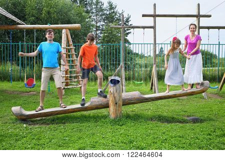 Parents with son and daughter teetering on a swing on a wooden playground