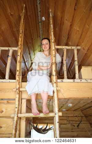 Barefoot beautiful woman is sitting on top of a wooden staircase in a wooden house